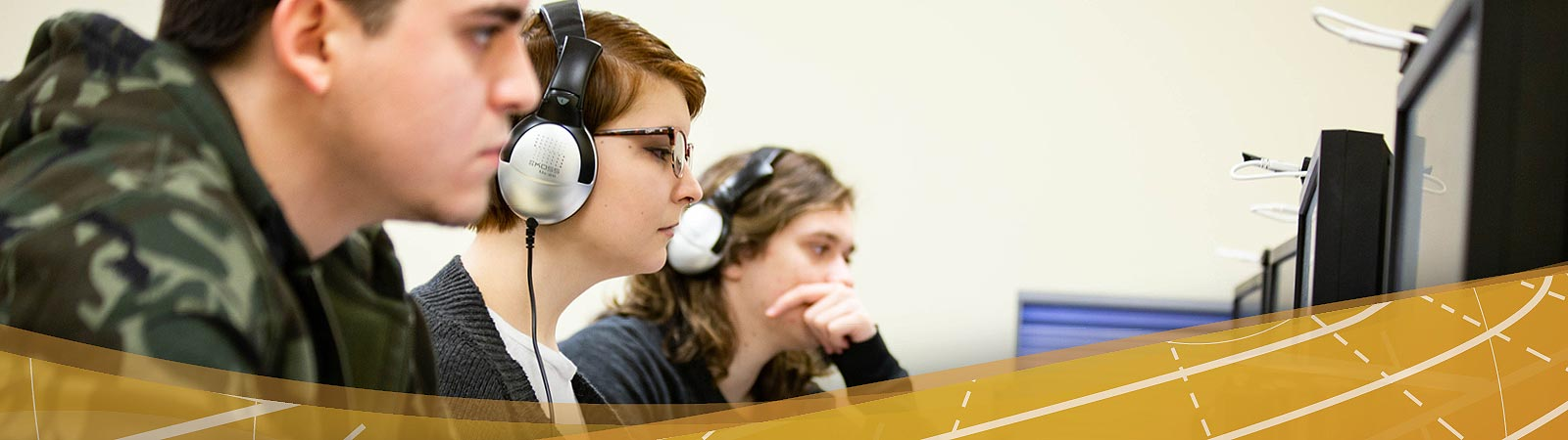 Students wearing headphones while working on digital video projects