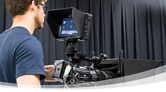 Student operating a video camera in a studio