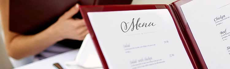 A restaurant menu being handed to a patron sitting at a table