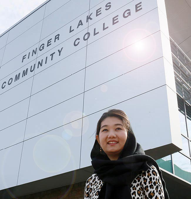 Student walking near the Finger Lakes Community College sign