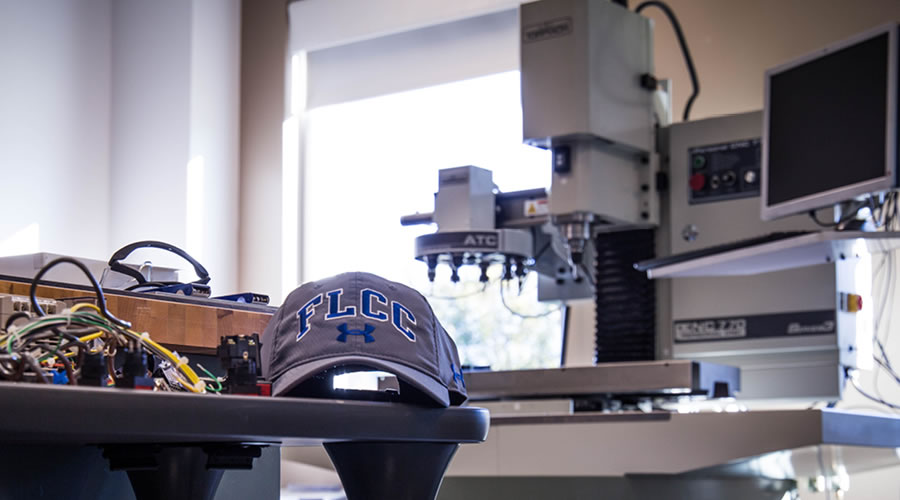 FLCC hat with large scale CNC milling machine in background