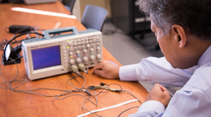 FLCC faculty member adjusting a digital oscilloscope for an electrical signal measurement