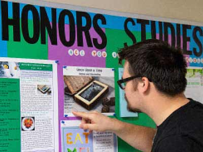 Student checking out Honors Studies learning opportunities on an information board